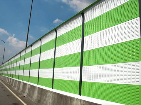 Green and white noise barriers are installed on the highway.