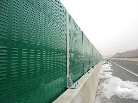 Green common shape noise barriers are installed on the highway.