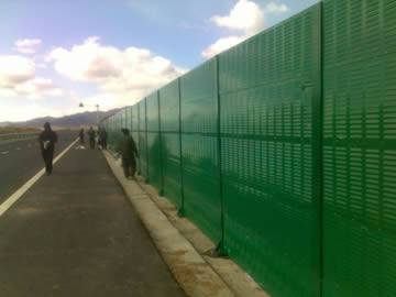 Green noise barriers are installed on the highway.