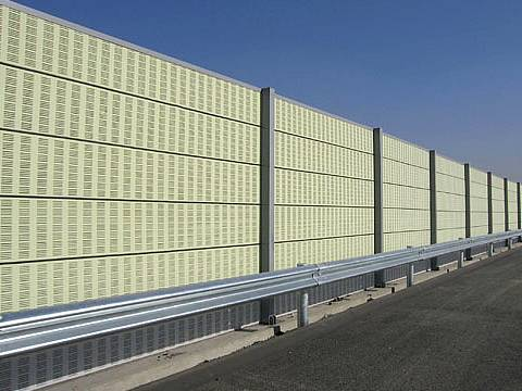 Yellow noise barriers are installed on the highway.