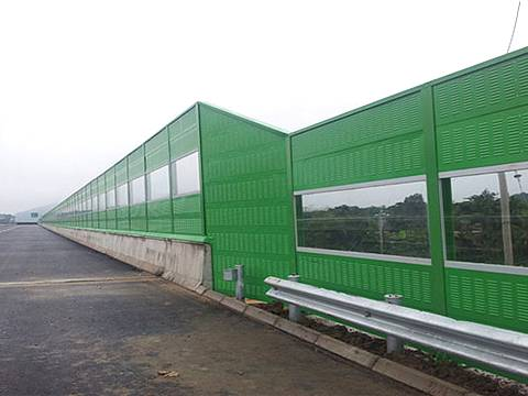 Green noise barrier with irregular shapes are installed on the highway.