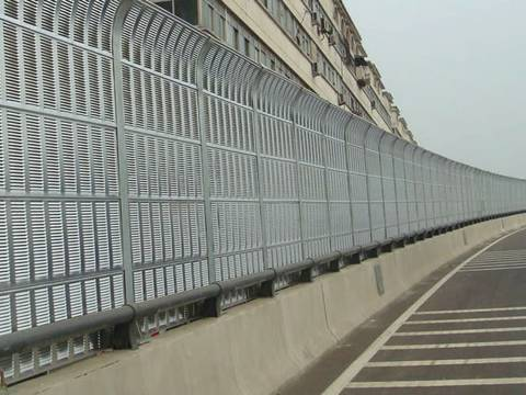 Top arc shaped noise barriers are installed on the highway.