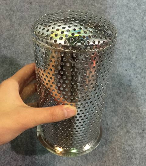 A hand holds a perforated cylinder filter and the bottom of the filter is also punched with round holes.