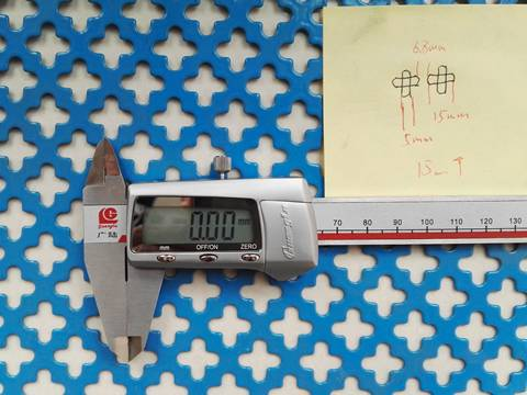 A vernier caliper is placed on a piece of blue color decorative perforated sheet with cross hole pattern.