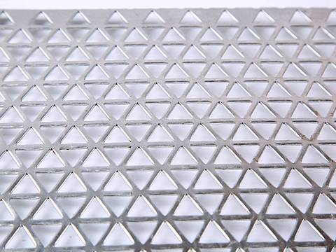 A piece of galvanized decorative perforated sheet with triangle hole patterns on the white background.
