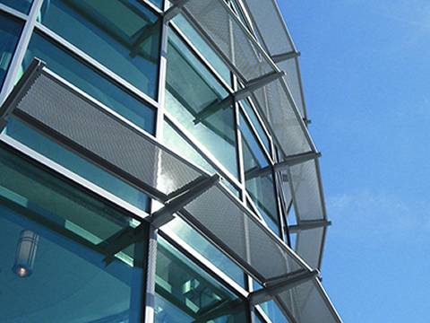 Horizontal perforated sunshade panels with margin are fitted on windows of glass wall high rise.