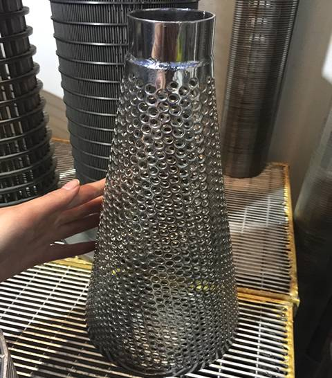 A galvanized steel cone filter with flat top is made of multilayer round perforated sheet.