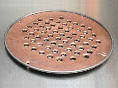 A filter made of perforated brass sheets with round holes