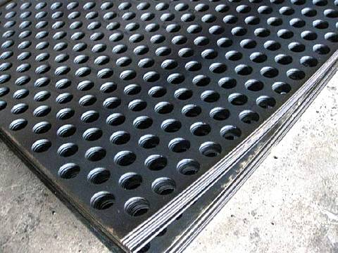 Some pieces of round hole perforated stainless steel sheets are placed on the ground
