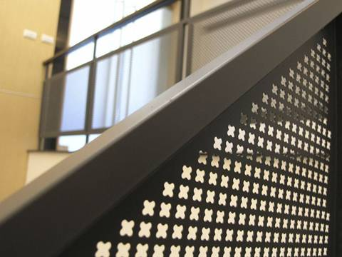 Brown stair banister made of decorative perforated sheet with cross-shaped holes