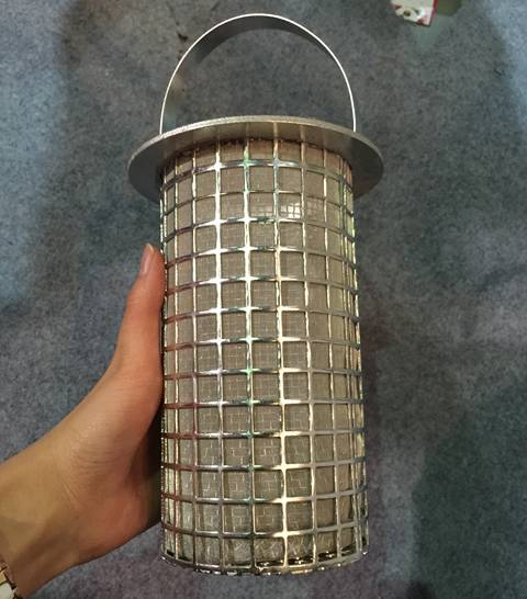 A hand holds a basket filer with perforated square holes outside and woven wire mesh inside.
