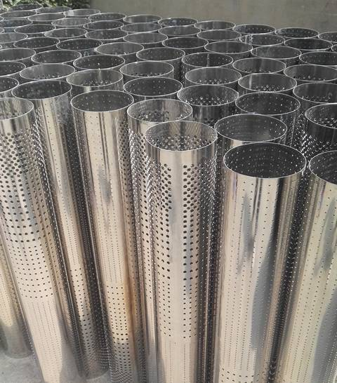There are many perforated filters standing on the ground, and there are at least four kinds of openings on each one.