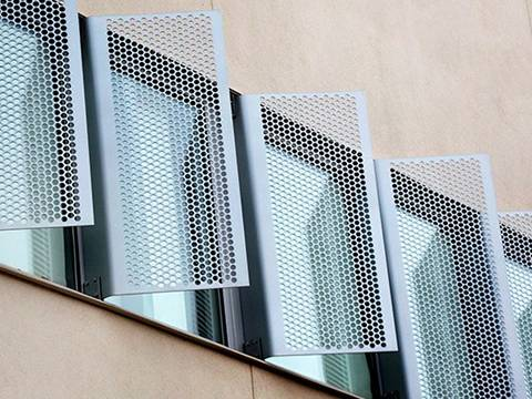 Six vertical perforated sunshade panels with hexagonal hole is installed on the windows.